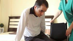 Hombre joven en la silla de ruedas que transfiere en cama