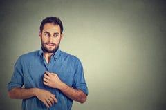Hombre joven en la situación desagradable, torpe, jugando nervioso con las manos vergu|enza fotografía de archivo