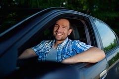 Hombre joven en la sonrisa del coche Imagen de archivo libre de regalías