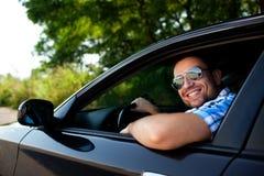 Hombre joven en la sonrisa del coche Imagenes de archivo