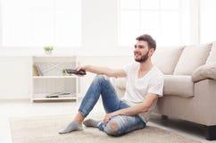 Hombre joven en la TV de observación casual en casa imagenes de archivo