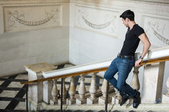 Hombre joven en la verja en el edificio maravillosamente adornado Fotos de archivo
