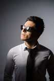 Hombre joven en las gafas de sol frescas aisladas en gris Fotos de archivo libres de regalías