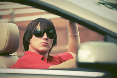 Hombre joven en las gafas de sol que conducen el coche convertible Imagen de archivo