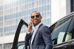 Hombre joven en las gafas de sol que se inclinan en el coche que tiene conversación sobre el primer alegre sonriente del smartpho imagen de archivo