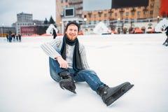 Hombre joven en los patines que se sientan en el hielo, pista de patinaje Imagen de archivo libre de regalías