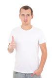 Hombre joven en los pulgares blancos de la camiseta para arriba aislados en blanco Fotografía de archivo libre de regalías