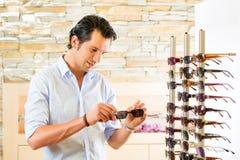 Hombre joven en los vidrios de sol de compra del óptico imagen de archivo libre de regalías