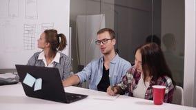 Hombre joven en los vidrios y dos mujeres que discuten algo con uno a mientras que se sienta en la tabla de la oficina en creativ metrajes