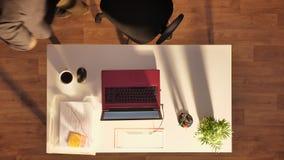 Hombre joven en los vidrios y el traje que se sientan detrás del escritorio con el ordenador portátil y el café, saliendo, tiro s almacen de video