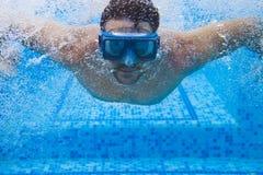 Hombre joven en máscara del salto que nada el arrastre delantero en una piscina, Tak Imagenes de archivo