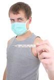 Hombre joven en máscara protectora con el termómetro Imagenes de archivo