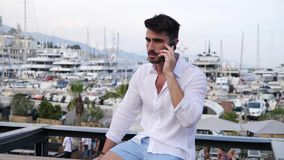 Hombre joven en Mónaco que habla en el teléfono móvil metrajes