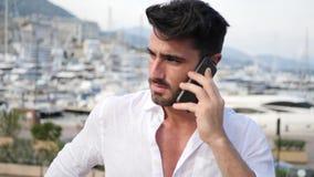 Hombre joven en Mónaco que habla en el teléfono móvil almacen de video