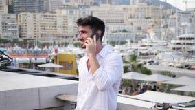 Hombre joven en Mónaco que habla en el teléfono móvil almacen de metraje de vídeo