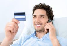 Hombre joven en móvil con de la tarjeta de crédito Fotos de archivo libres de regalías