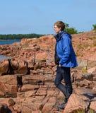 Hombre joven en orilla rocosa Foto de archivo libre de regalías