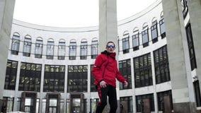 Hombre joven en rap rojos del equipo y de las gafas de sol del deporte al lado de columnas del granito almacen de metraje de vídeo