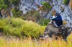 Hombre joven en roca de la montaña imagen de archivo