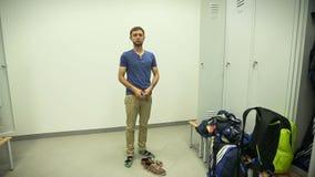 Hombre joven en ropa cambiante del vestuario del gimnasio, competencia atlética aficionada almacen de metraje de vídeo