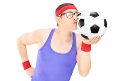 Hombre joven en ropa de deportes que besa un fútbol Imágenes de archivo libres de regalías