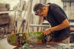 Hombre joven en rueda de la fijación del taller de la carpintería en su monopatín Fotografía de archivo
