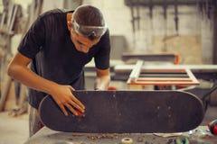 Hombre joven en rueda de la fijación del taller de la carpintería en su monopatín Fotos de archivo libres de regalías