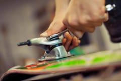 Hombre joven en rueda de la fijación del taller de la carpintería en su monopatín Imagenes de archivo
