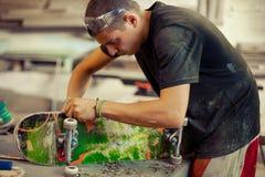 Hombre joven en rueda de la fijación del taller de la carpintería en su monopatín Fotos de archivo