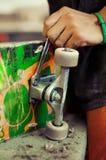 Hombre joven en rueda de la fijación del taller de la carpintería en su monopatín Foto de archivo