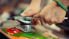 Hombre joven en rueda de la fijación del taller de la carpintería en su monopatín Foto de archivo libre de regalías