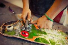 Hombre joven en rueda de la fijación del taller de la carpintería en su monopatín Imagen de archivo libre de regalías