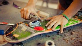 Hombre joven en rueda de la fijación del taller de la carpintería en su monopatín Imagen de archivo