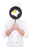 Hombre joven en sartén que se sostiene uniforme del cocinero con freír el huevo detrás Imagen de archivo