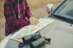 Hombre joven en sombrero con el mapa de camino y los prismáticos que buscan el camino correcto f foto de archivo libre de regalías