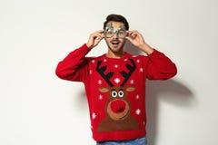 Hombre joven en suéter de la Navidad con los vidrios del partido fotos de archivo libres de regalías