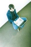 Hombre joven en suelo con la computadora portátil Imágenes de archivo libres de regalías