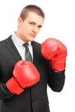 Hombre joven en traje con los guantes de boxeo rojos listos para luchar Imagen de archivo