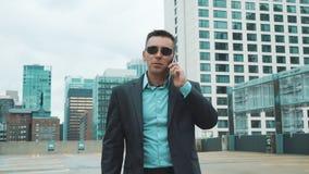 Hombre joven en traje que habla en el tel?fono en ciudad Hombre de negocios hermoso en juego almacen de metraje de vídeo