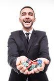 Hombre joven en traje que soporta las fichas de póker del triunfo en el juego Fotografía de archivo