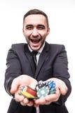 Hombre joven en traje que soporta las fichas de póker del triunfo Victoria en el juego Imagenes de archivo