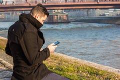 Hombre joven en un abrigo de invierno negro que se sienta en el Riverbank y el Lo Foto de archivo