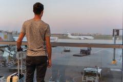 Hombre joven en un aeropuerto que mira los aviones antes de salida imagenes de archivo