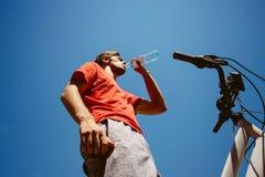 Hombre joven en un agua de la bebida de la bicicleta de debajo tiro imagen de archivo