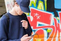 Hombre joven en un casquillo con un teléfono móvil Foto de archivo libre de regalías