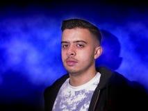 Hombre joven en un fondo azul imagen de archivo libre de regalías
