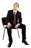 Hombre joven en un juego de asunto negro que se sienta en un ch Fotos de archivo