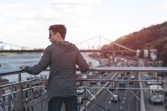 Hombre joven en un puente en una ciudad grande Fotos de archivo libres de regalías