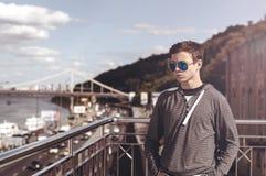 Hombre joven en un puente en una ciudad grande Foto de archivo