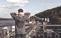 Hombre joven en un puente en una ciudad grande Fotos de archivo